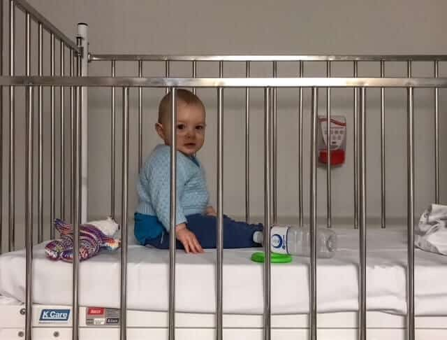 Baby in a hospital cot